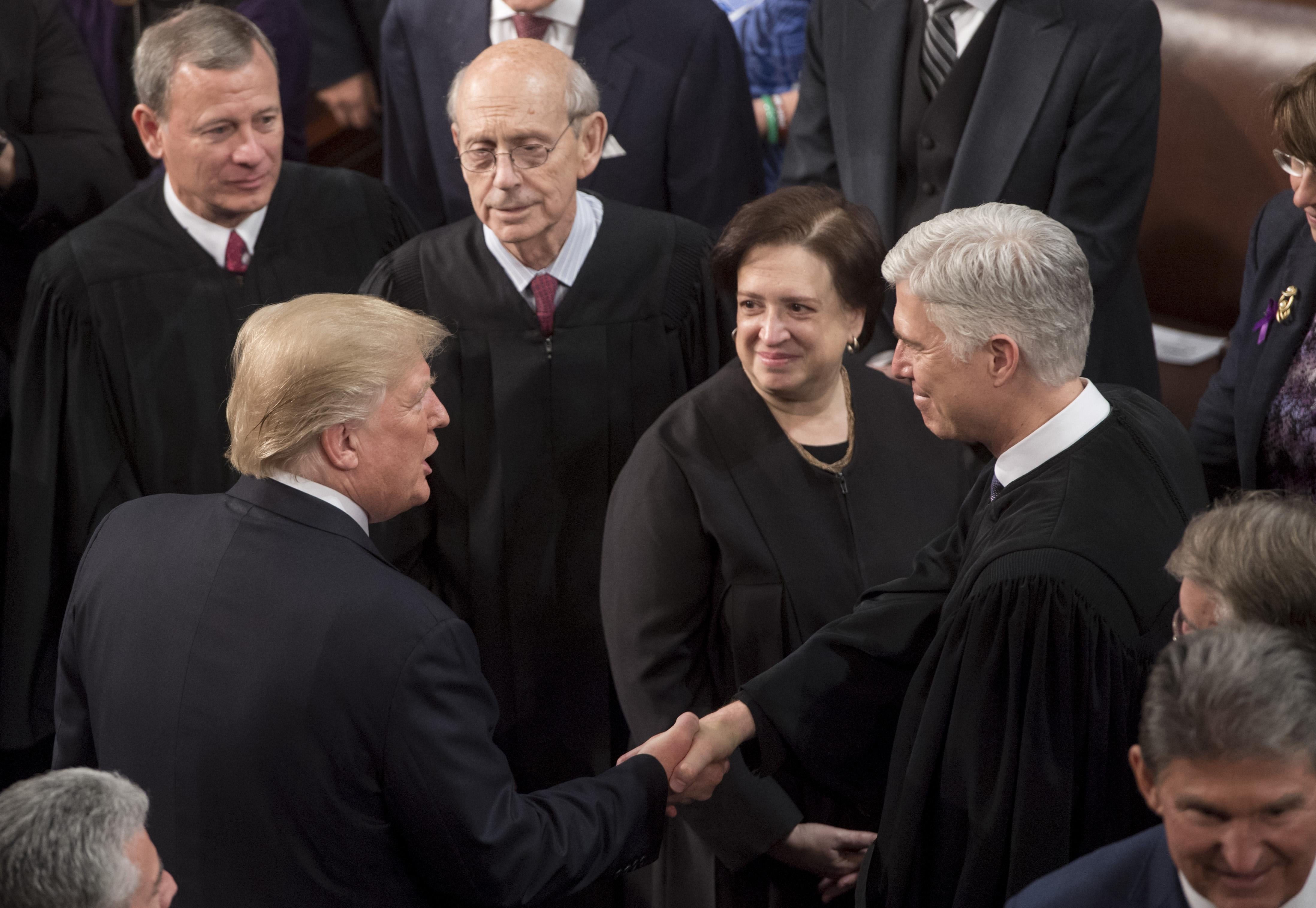 US President Donald Trump shakes hands with Supreme Court Justice Neil Gorsuch (R) alongside US Supreme Court Chief Justice John Roberts (L), Justice Stephen Breyer (2L), and Elena Kagan (2R), during the State of the Union Address before a Joint Session of Congress at the US Capitol in Washington, DC, January 30, 2018. / AFP PHOTO / SAUL LOEB        (Photo credit should read SAUL LOEB/AFP/Getty Images)
