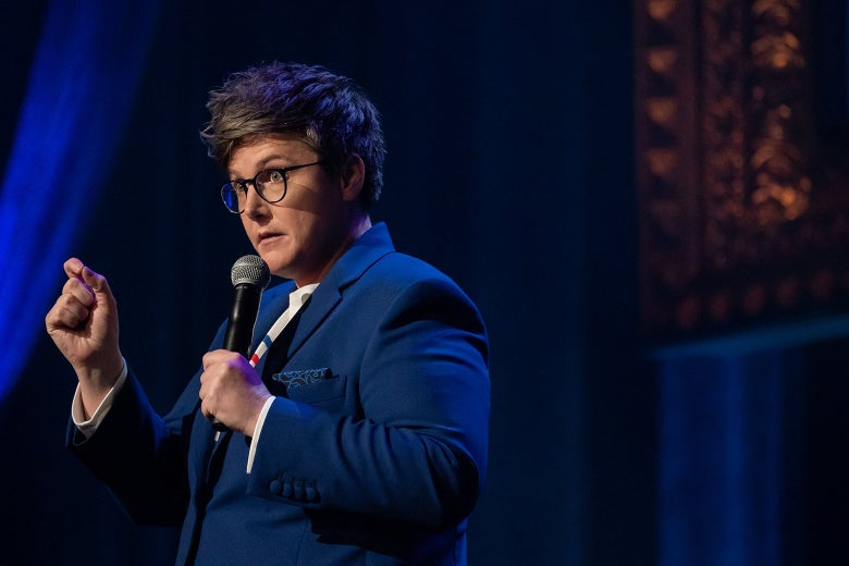 Hannah Gadsby on stage, in a blue jacket and striped shirt, holding a mic.