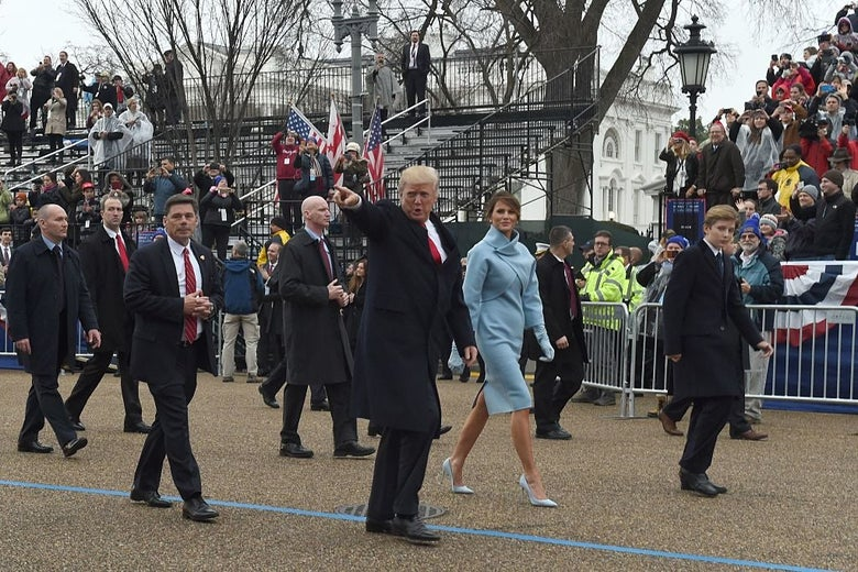 Donald Trump, who is pointing, Melania Trump, Barron Trump, and security officials walk past a mostly empty set of bleachers during the inaugural parade.