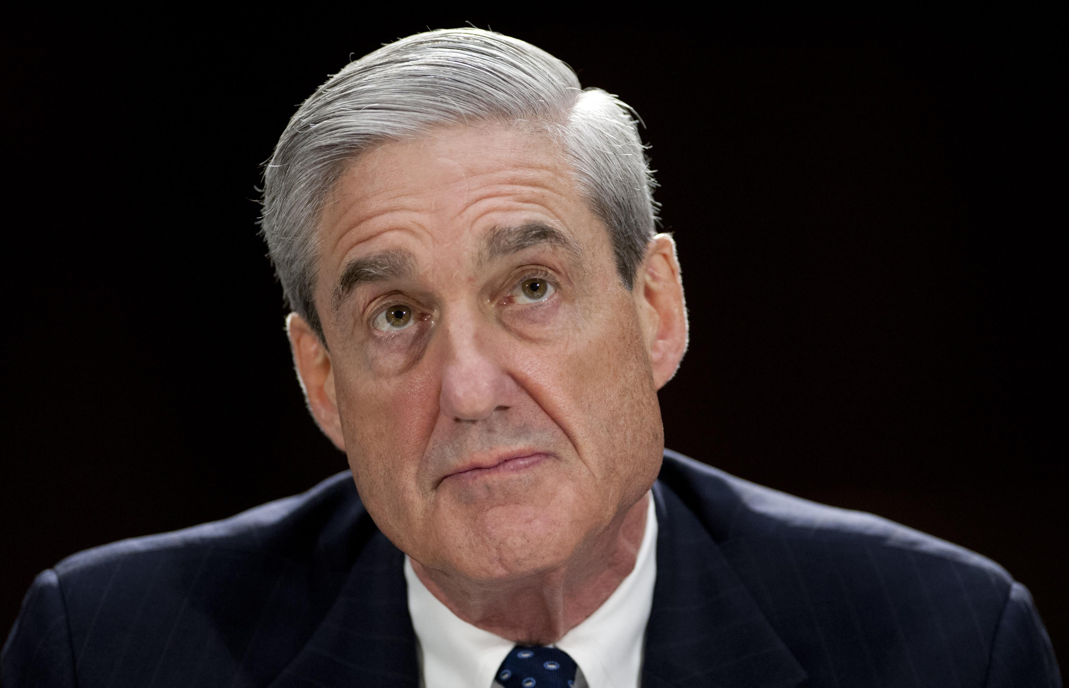 Mueller, in front of a background of black, looks upward.