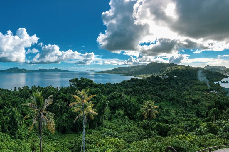 A landscape of lush forest, a lagoon, and a blue sky with white clouds.