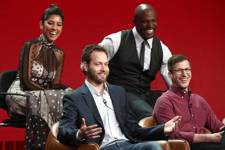 Dan Goor and Andy Samberg sit in front of Stephanie Beatriz and Terry Crews, talking animatedly.