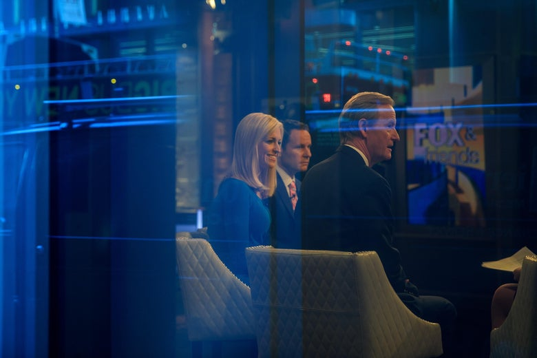 Seen through a window, (L to R) hosts Ainsley Earhardt, Brian Kilmeade and Steve Doocy broadcast 'Fox And Friends' from the Fox News studios, February 17, 2017 in New York City. President Trump, a frequent consumer and critic of cable news, recently tweeted that Fox and Friends is 'great'. (Photo by Drew Angerer/Getty Images)