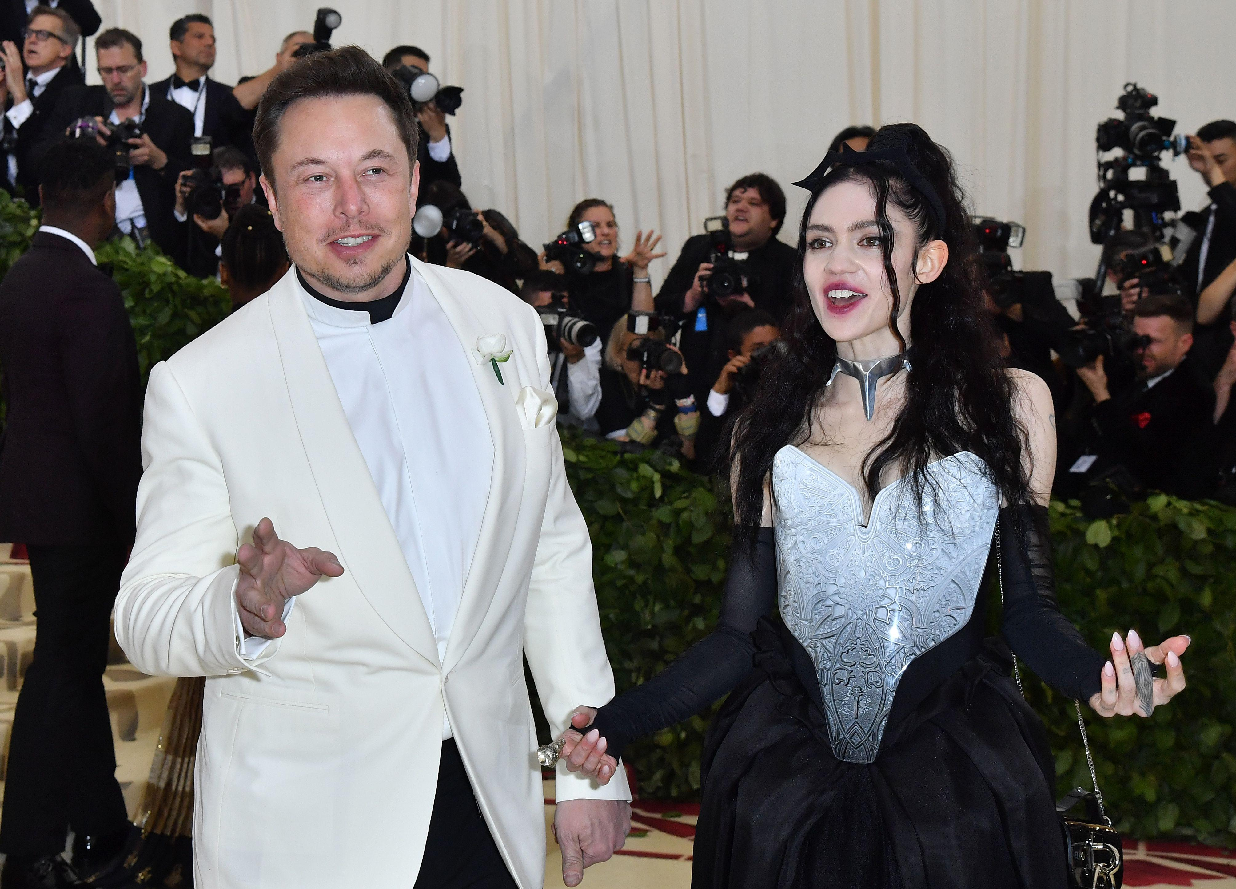 Elon Musk and Grimes arrive for the 2018 Met Gala on May 7, 2018, at the Metropolitan Museum of Art in New York. - The Gala raises money for the Metropolitan Museum of Arts Costume Institute. The Gala's 2018 theme is Heavenly Bodies: Fashion and the Catholic Imagination. (Photo by ANGELA WEISS / AFP)        (Photo credit should read ANGELA WEISS/AFP/Getty Images)