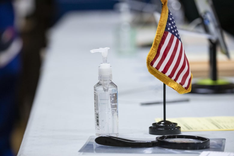 A bottle of hand sanitizer stands next to a small American flag on a table.