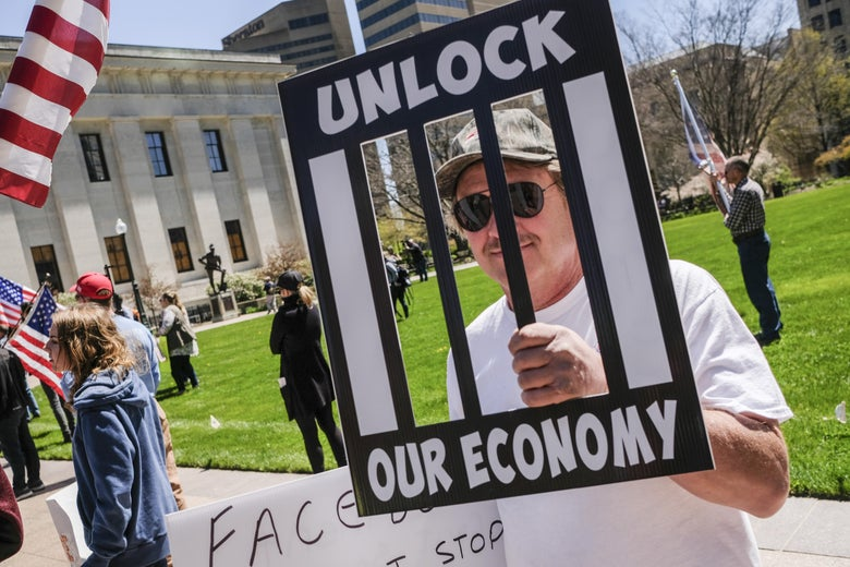 "A man in a white t-shirt and sunglasses carries a sign that reads ""UNLOCK OUR ECONOMY."""