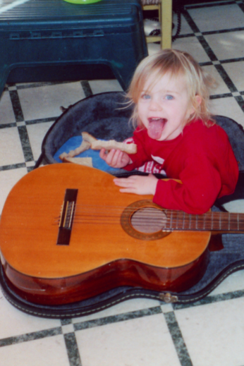 A young, blonde-haired girl sticks her tongue out at the camera, holding a sandwich crust and leaning on an adult-size guitar.