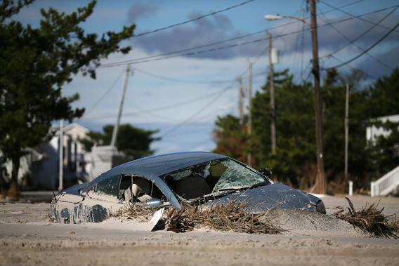 A car is buried in sand that was washed in from Hurricane Sandy on October 31, 2012 in Long Beach Island, New Jersey.