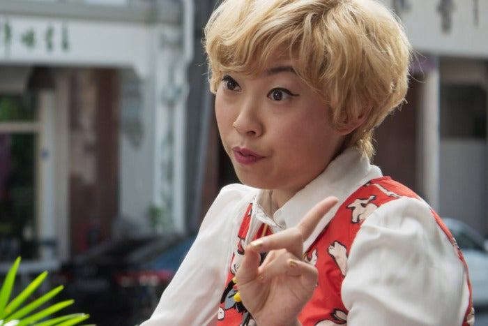 Awkwafina wears a short blonde wig and holds up a finger to someone off-camera.