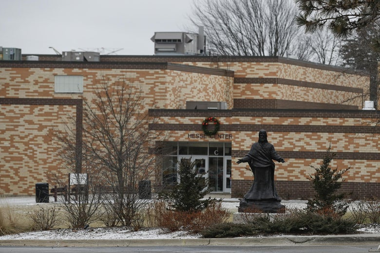 A high school exterior with a statue of the Virgin Mary in front