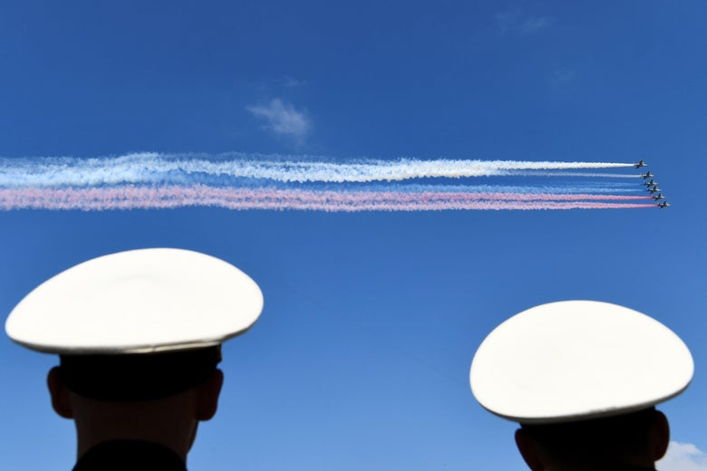 Russian aircraft release smoke in white, blue, and red, the colors of the Russian flag, while flying above the Neva River during the Navy Day parade in Saint Petersburg on July 29, 2018.
