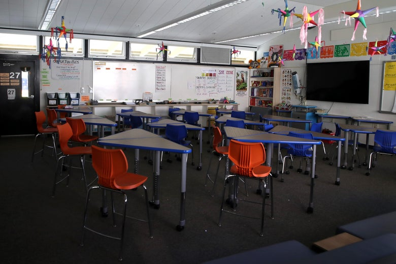 An empty classroom. Chairs, desks, a whiteboard, and a screen are seen within.