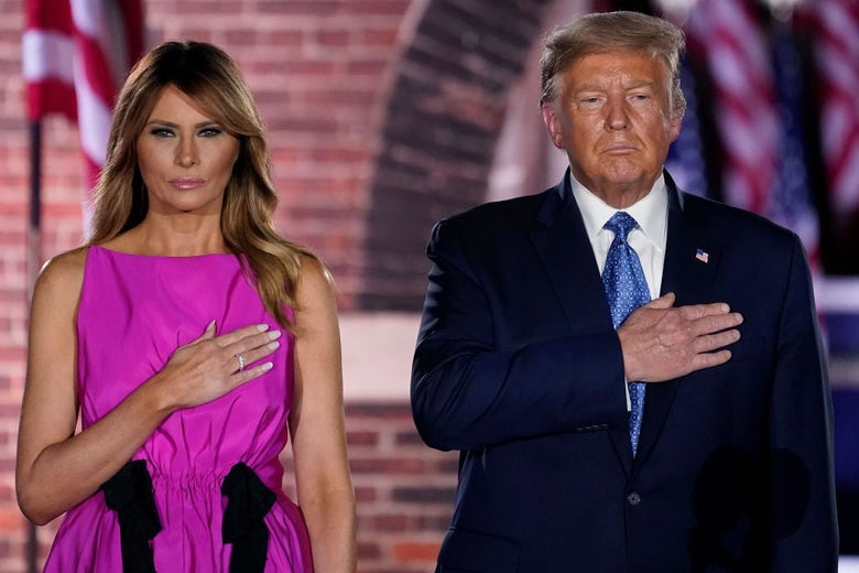 The Trumps, lit by stage lights, stand side by side in front of a brick arch holding their hands over their hearts.