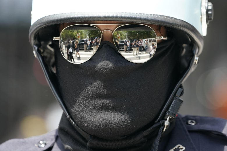 A man in a helmet, mask, and mirrored sunglasses wearing a mask that
