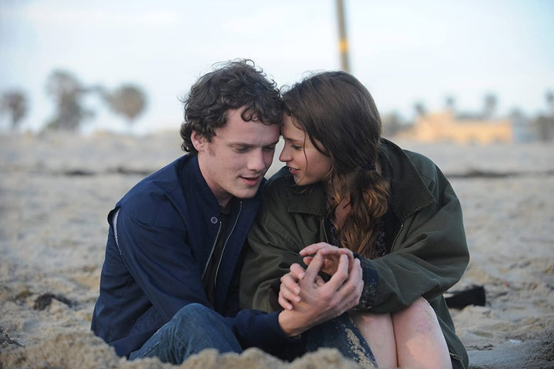 Anton Yelchin and Felicity Jones sit on a beach.