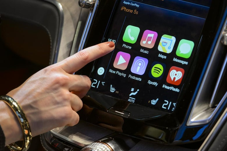 A finger reaches to touch an iPhone display on a screen inside a car.