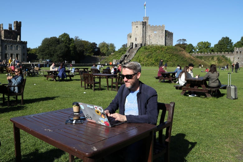 A man poses with his laptop computer in the late summer sunshine in the grounds of Cardiff Castle.