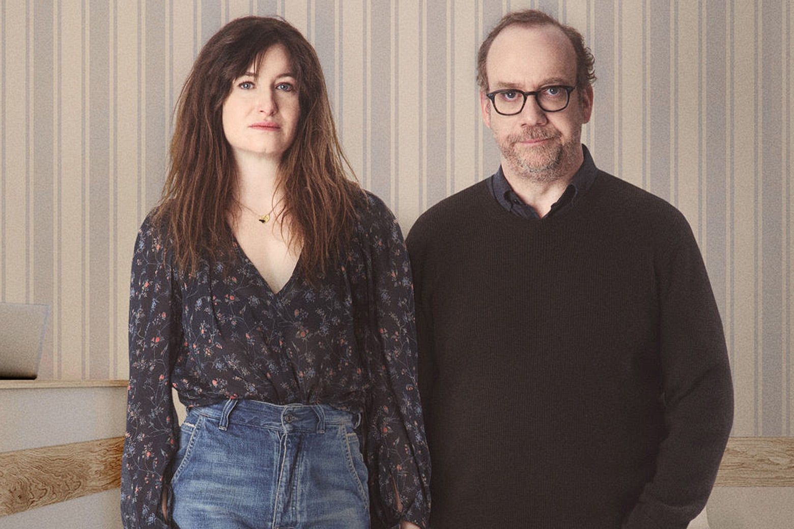 Kathryn Hahn and Paul Giamatti stand with neutral expressions in this Private Life photo.