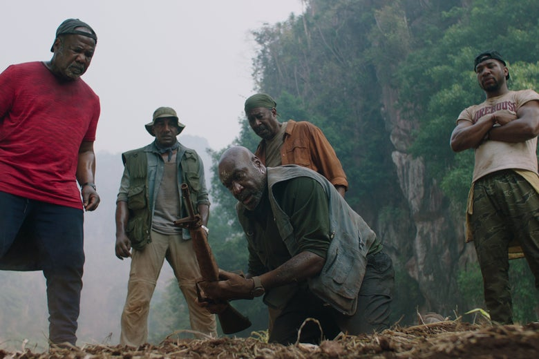 Men gather around Delroy Lindo as he lifts a rifle from the ground