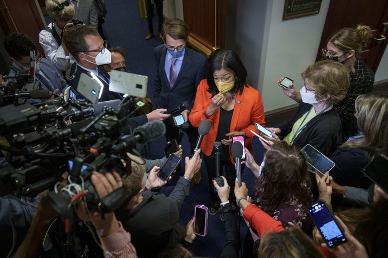 Jayapal standing in a hallway at the Capitol surrounded by reporters holding out phones and microphones for interviews