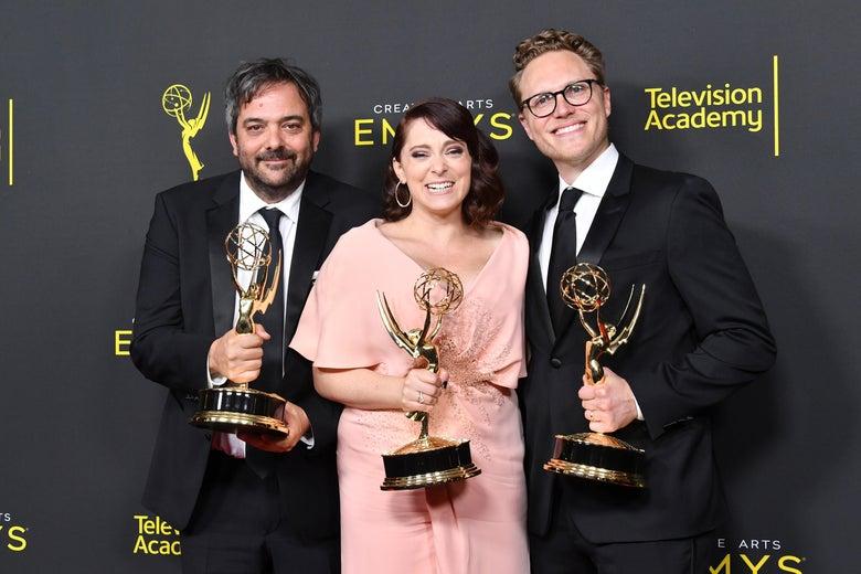 Adam Schlesinger, Rachel Bloom and Jack Dolgen pose with Emmys on a red carpet.