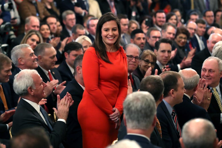 Stefanik stands and smiles as people seated close together around her applaud, some smiling at her