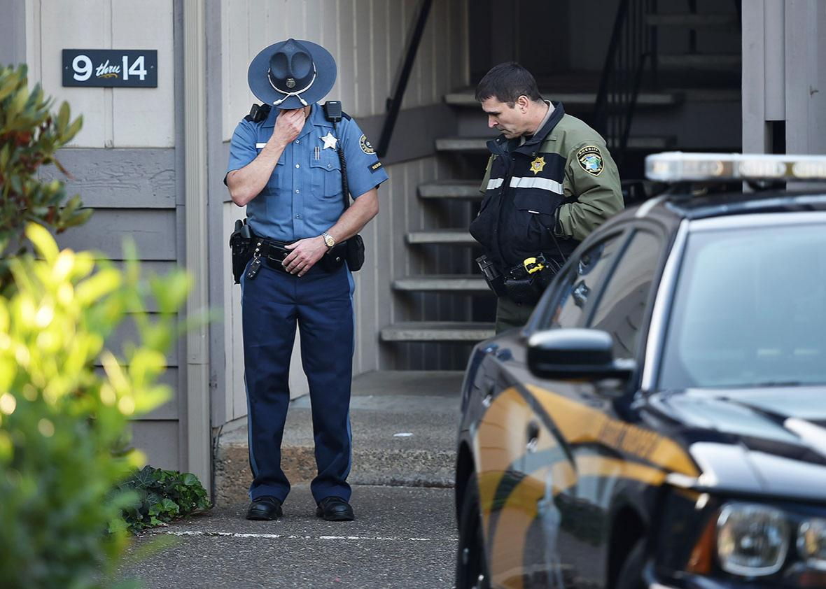 Police officers stand guard outside the apartment building where the alleged gunman, Chris Harper Mercer, lived in Winchester outside Roseburg, Oregon, on October 2, 2015.