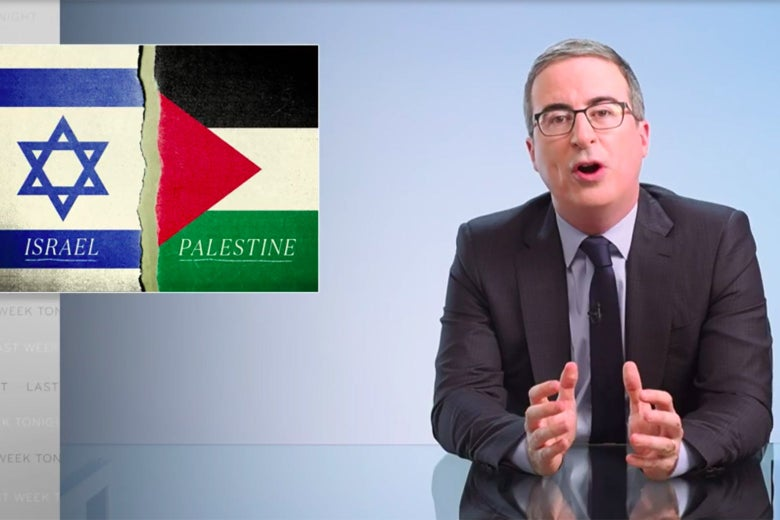 John Oliver sits at his glass anchorperson desk, in front of a graphic showing Israeli and Palestinian flags.