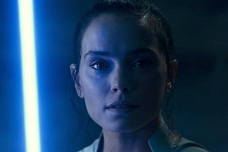 Daisy Ridley with a blue lightsaber to her left.