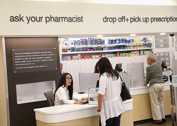 Pharmacist Jeanie Kim, left, consults with a customer at a Walgreens pharmacy on September 19, 2013 in Wheeling, Illinois.