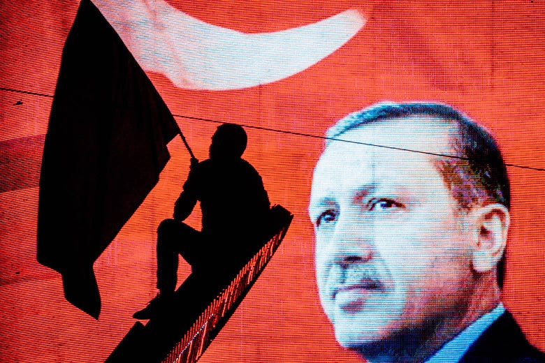 A man in silhouette waves a flag against the background of an electronic billboard depicting Erdogan and the Turkish flag.