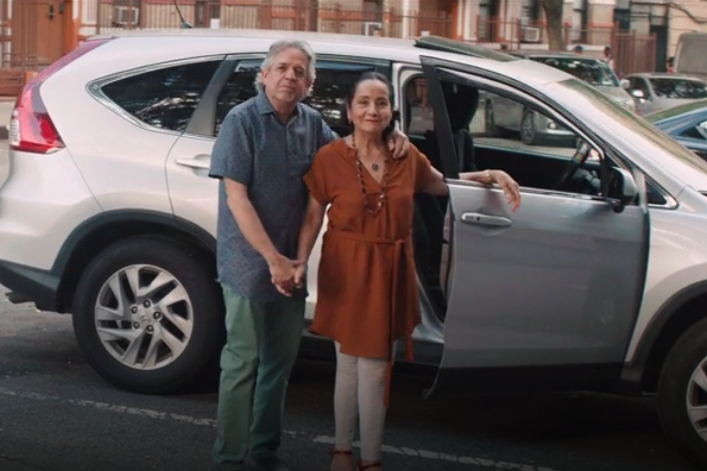 Standing in front of a silver car, Luis Miranda has his arm around Dr. Luz Towns-Miranda.