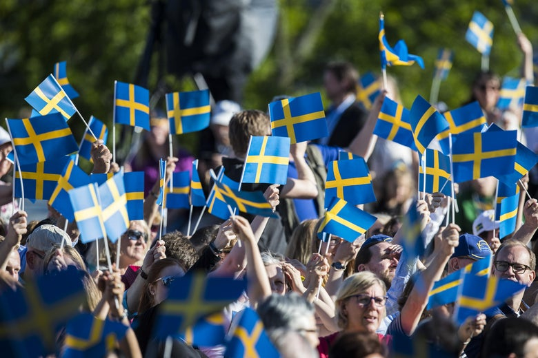 A group of people waves small Swedish flags, which are blue with a yellow crosses, during the national day celebrations at Skansen on June 6, 2017 in Stockholm, Sweden.