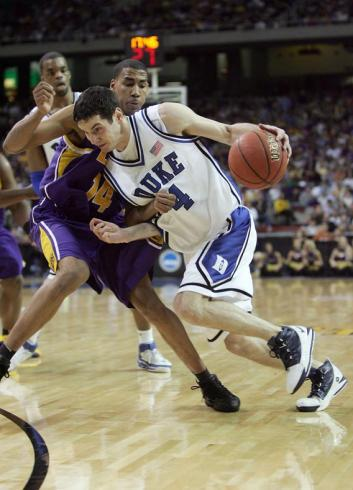 J.J. Redick #4 of the Duke Blue Devils dribbles against Garrett Temple #14 of the LSU Tigers.