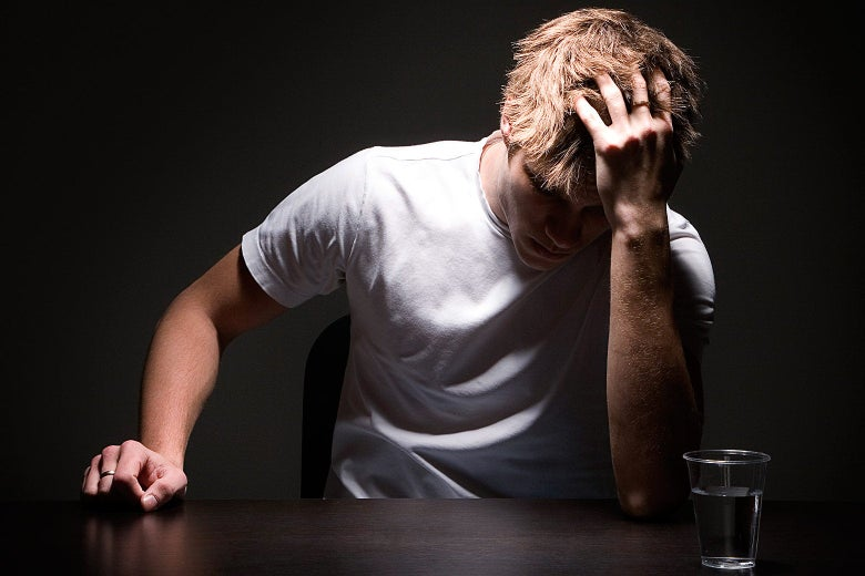 A college-age man clutching his head in frustration in a dark interrogation room.