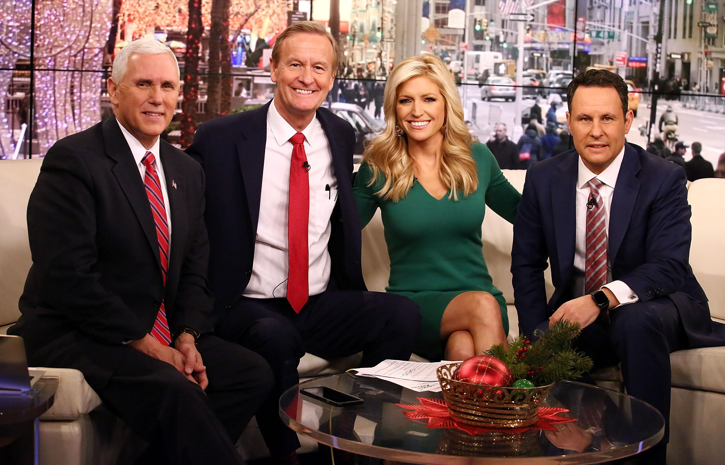 Steve Doocy, Ainsley Earhardt and Brian Kilmeade pose and smile in a studio.