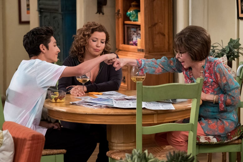 Marcel Ruiz as Alex, Justina Machado as Penelope, and Rita Moreno as Lydia, seated at a table in a scene from One Day at a Time. Alex and Lydia fist-bump across the table in front of Penelope.