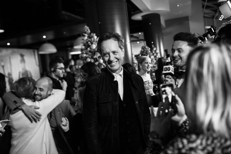 A black-and-white photo of Richard E. Grant smiling, surrounded by other people on a crowded red carpet for a movie premiere in November 2018.