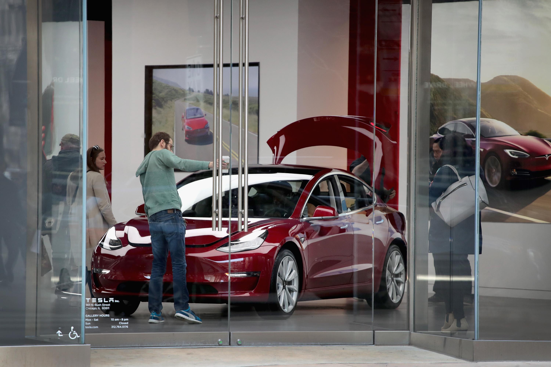 A Model 3 sits on the showroom floor at a Tesla dealership.