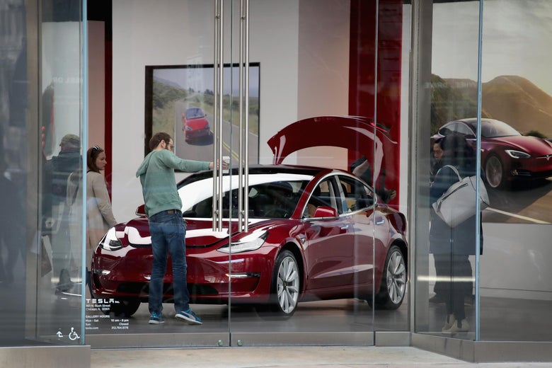 A Model 3 sits on the showroom floor at a Tesla dealership.