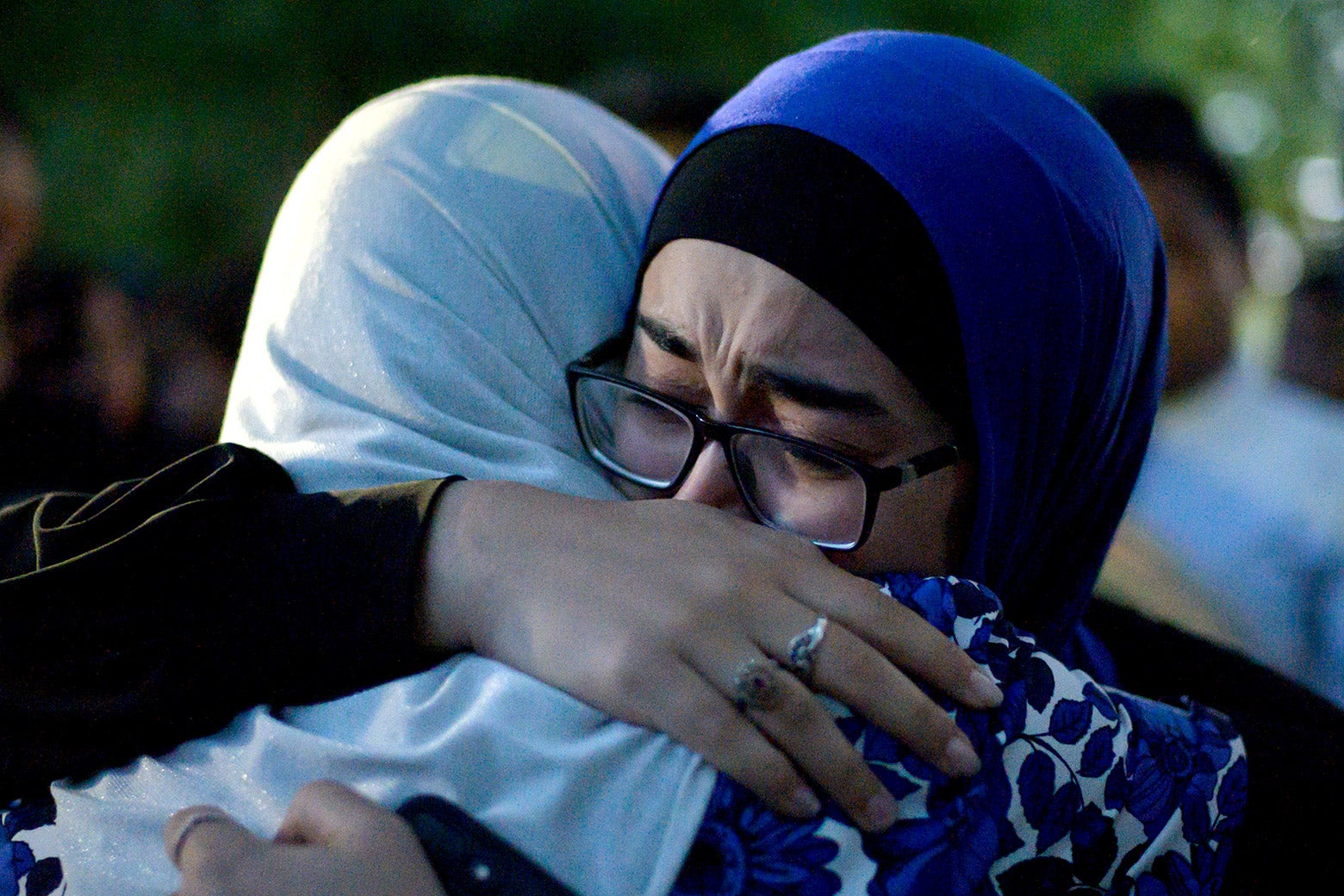 Two women wearing head scarves cry and hug.