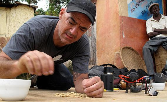 Todd Carmichael inspects the coffee beans as a local man looks on in Haiti on 'Dangerous Grounds.'