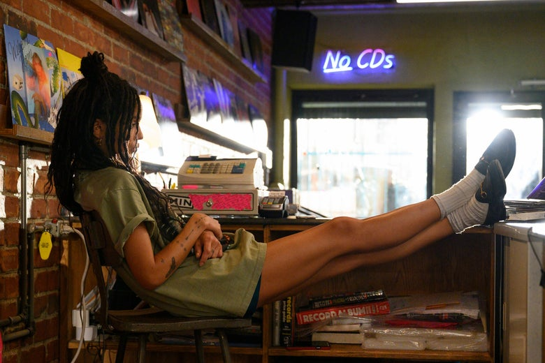 "Zoë Kravitz in a scene from High Fidelity, in which she sits at a cash register while a ""No CDs"" neon sign blares in the background."