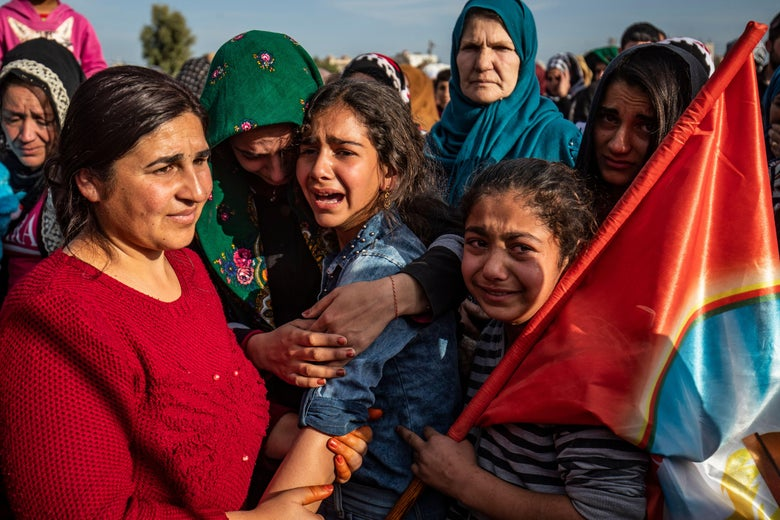 Women and children crying. One is holding a flag.