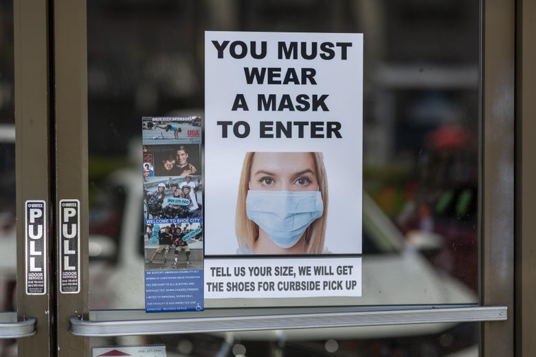 "A sign on a glass door says ""You must wear a mask to enter"" and shows a photo of a woman wearing a face mask."