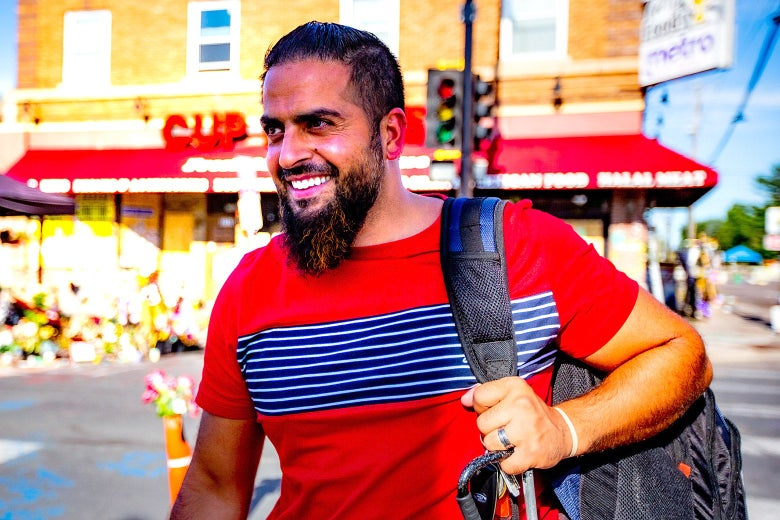 Mahmoud Abumayyaleh in a red T-shirt with a backpack over one shoulder. The CUP Foods store is behind him.