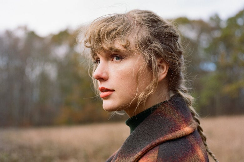 Taylor Swift, in a wintry field, in a braid and a plaid coat.