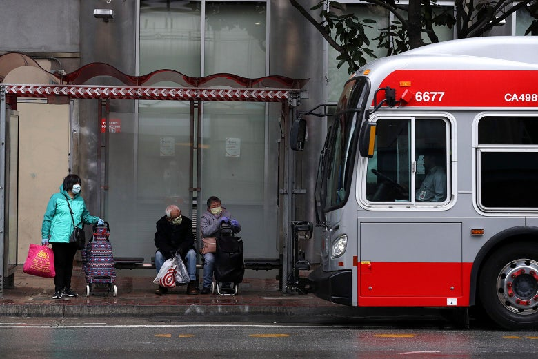 Riders, in face masks, wait for a MUNI bus as it pulls into a stop in San Francisco. Looks like a gray day.