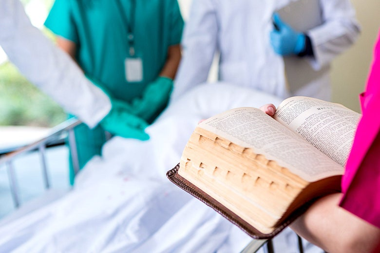 Doctors stand at the foot of a bed and put their hands on a patient's body. Across from the, a person holds open a heavy book.