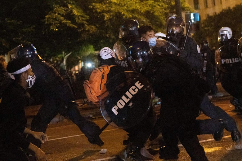Police charge at protesters on a dark street.